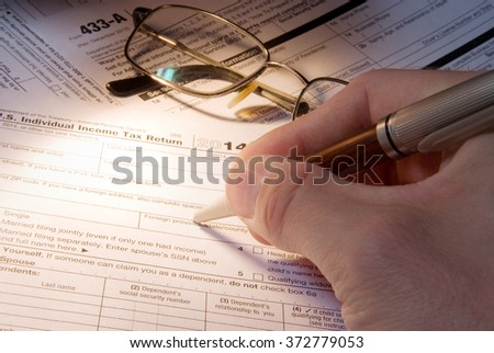 Tax form business financial concept - hand filling in individual return tax form - stock photo