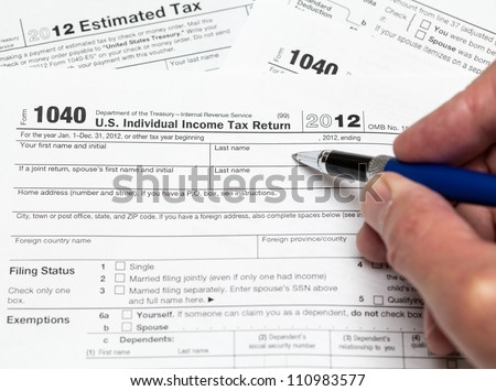 Tax form 1040 for tax year 2012 for US individual tax return with hand - stock photo