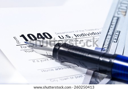 Tax form 1040 on a gray background, blue pen, and 100 dollar bills out of focus - stock photo
