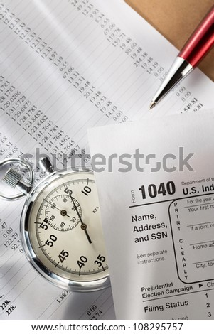 Tax form, operating budget and stopwatch - stock photo