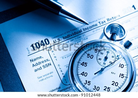 Tax form, pen and stopwatch - stock photo