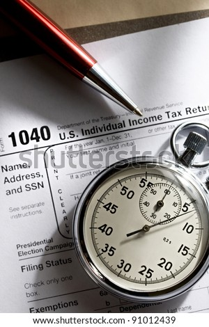 Tax form, red pen and stopwatch - stock photo
