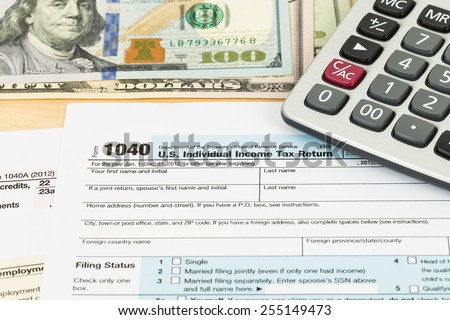 Tax form with banknote, and calculator - stock photo