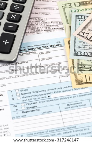 Tax form with calculator and banknote taxation concept - stock photo