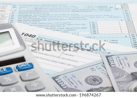 Tax Form 1040 with calculator and US dollars - stock photo