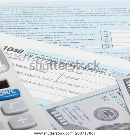 Tax Form 1040 with calculator and US dollars - 1 to 1 ratio - stock photo