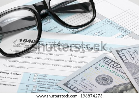 Tax Form 1040 with dollars and glasses - stock photo