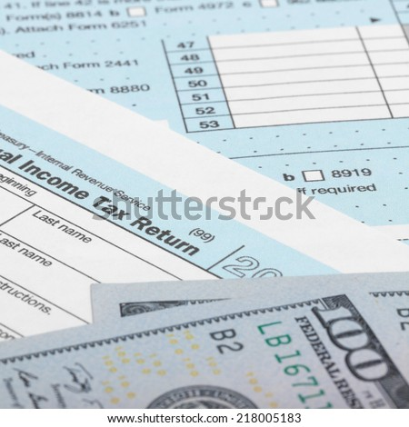 Tax Form 1040 with 100 US dollar bills - 1 to 1 ratio - stock photo