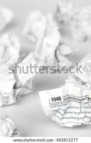 Tax forms balled and thrown away in frustration - stock photo
