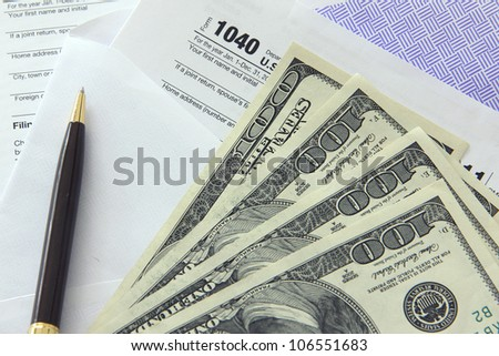 Tax papers in an envelope with 100 dollar bills - stock photo