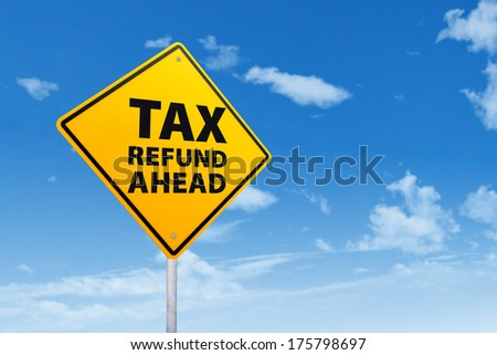 Tax refund concept with a road sign under blue sky - stock photo