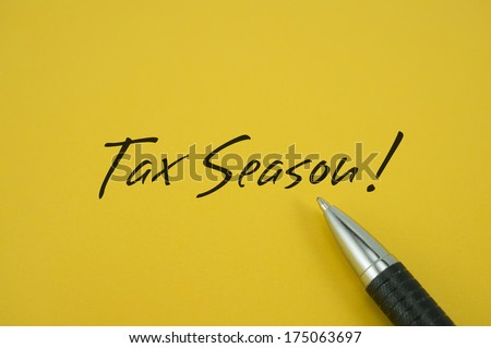 Tax Season! note with pen on yellow background - stock photo
