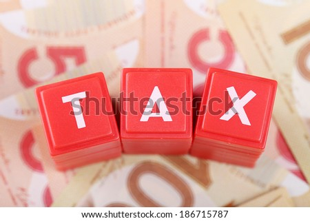 Tax word on money background  - stock photo