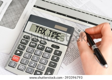 Taxation time concept with hand calculator and tax form - stock photo