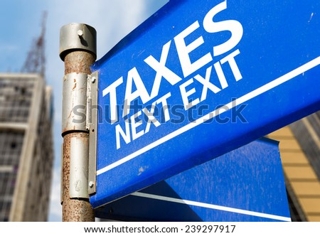 Taxes Next Exit blue road sign - stock photo