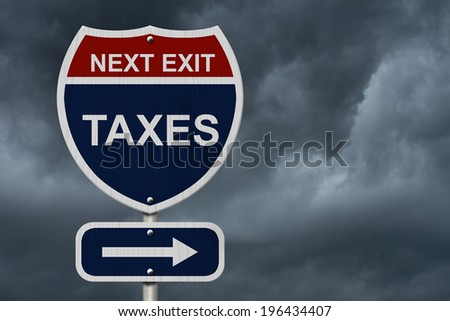 Taxes this way, Blue and Red Interstate Sign with word Taxes and an arrow with stormy sky background - stock photo