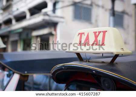 Taxi is called Tuk-Tuk scooters. Bangkok, Thailand. (selective focus on Taxi sign on roof) - stock photo