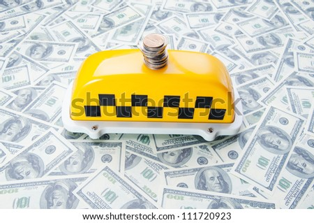 Taxi sign with stack of coins on one hundred dollar bills, studio shot - stock photo
