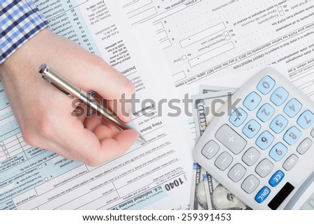 Taxpayer filling out USA 1040 Tax Form - stock photo