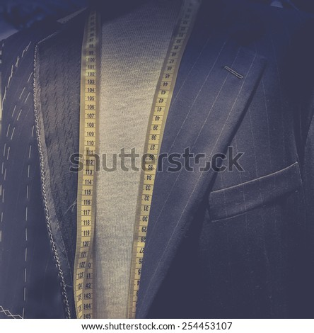 Taylor made men's designer suit - tape measure - stock photo