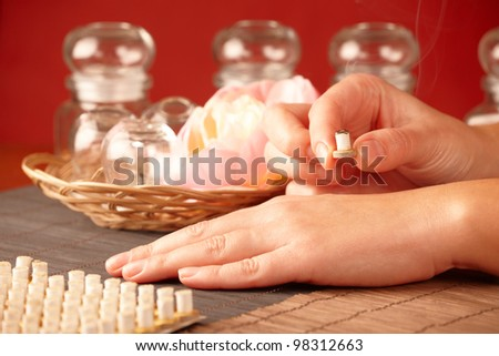 TCM Traditional Chinese Medicine. Hand applying mini moxa stick therapy, natural herbs in glass jars in background - stock photo
