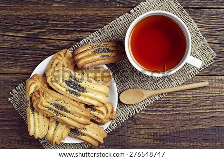 Tea and cookies with poppy Cup of tea and cookies with poppy in plate on old wooden table, top view  - stock photo