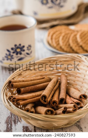 Tea and teapot with biscuit, cinnamon, clove and sugar - stock photo