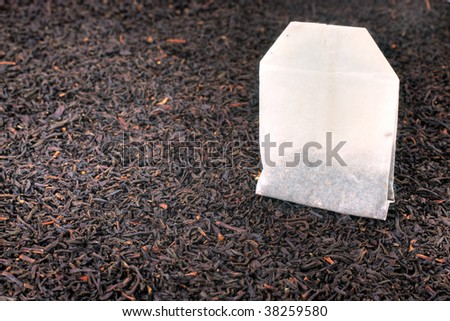 Tea bag and dried tea leaves. Macro still life with shallow dof. - stock photo