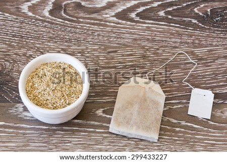 Tea bag and tea herbs in a bowl on wooden background - stock photo