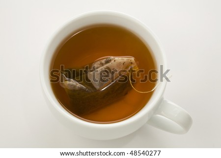 tea bag brewing in a white cup isolated on white - stock photo