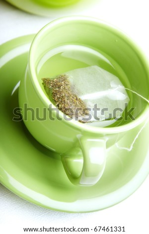 Tea bag in the green cup on a white background - stock photo