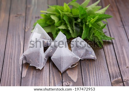 Tea bags  on wooden background. Fresh melissa, mint. Selective focus. - stock photo