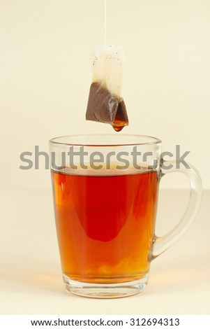 Tea bags over the glass with fresh fragrant tea - stock photo