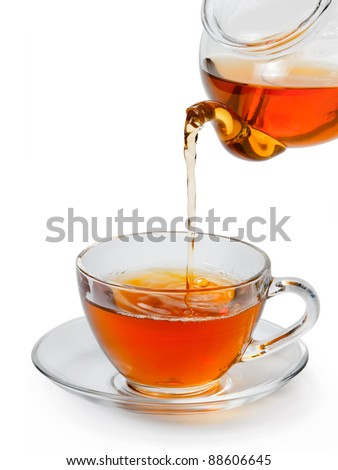 Tea being poured into glass tea cup isolated on a white background. - stock photo