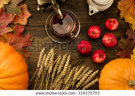 Tea c still life with samovar, apples, ripe orange pumpkins, maple leaves, wheat on wooden background. Thanksgiving, autumn. - stock photo