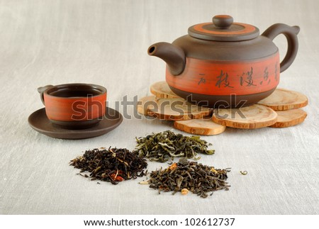 tea concept: piles of dry tea of different kinds, tea cup and kettle - stock photo