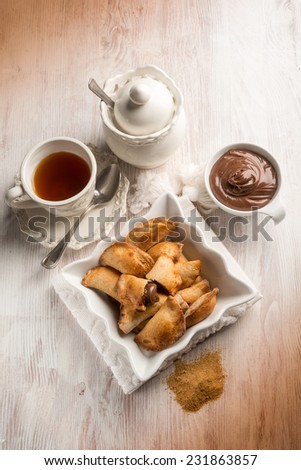 tea cup and cookie stuffed with chocolate cream - stock photo