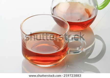 Tea Cup and Kettle on white reflective background - stock photo