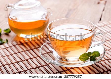 tea cup and teapot with green tea - stock photo