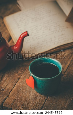 Tea cup with a red heart , teapot and an old journal on an old wooden desk - stock photo