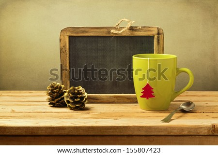Tea cup with paper Christmas tree and chalkboard on wooden table - stock photo
