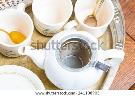 tea cups and jug on wooden table and silver plate - stock photo