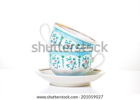 Tea cups and saucer on white background. Tea time. Porcelain ornamental  tea  set. Decorative background.  - stock photo