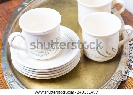 tea cups on wooden table and silver plate - stock photo
