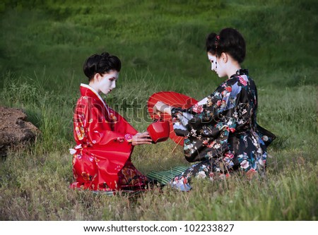 Tea drinking. Asian style portrait of two woman sitting on the grass and drinking tea - stock photo