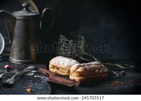 Tea drinking with eclairs and chopped chocolate, served with vintage teapot and cutlery over dark background. See series - stock photo