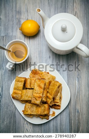 tea-drinking with homemade apple and raisins pie made of flaky pastry - stock photo