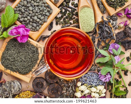 Tea glass cup and collection of different dry types tea (green,black, herbal) on wooden table background, top view  - stock photo