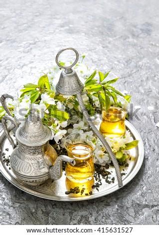 Tea glasses and pot. Oriental holidays decoration. Silver tea dishes. Herbal tea. Tea cups. Traditional tea. Tea pot. Tea service. Tea drink. Hot tea. Turkish tea. Arabic tea. Moroccan tea. Tea table - stock photo