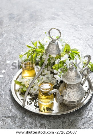 Tea glasses and pot. Oriental silver tableware. Spring flowers decoration - stock photo